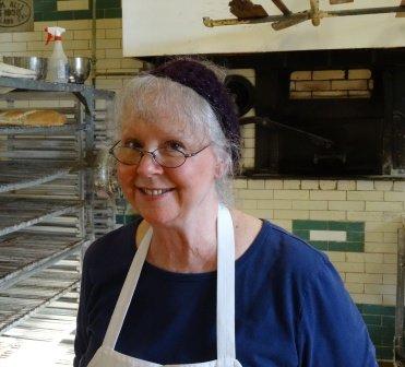 Dianne Hampton tending the brick oven at San Juan Bakery